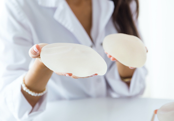 woman holding 2 breast implants